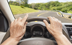 Senior woman driving a car slowly in highway